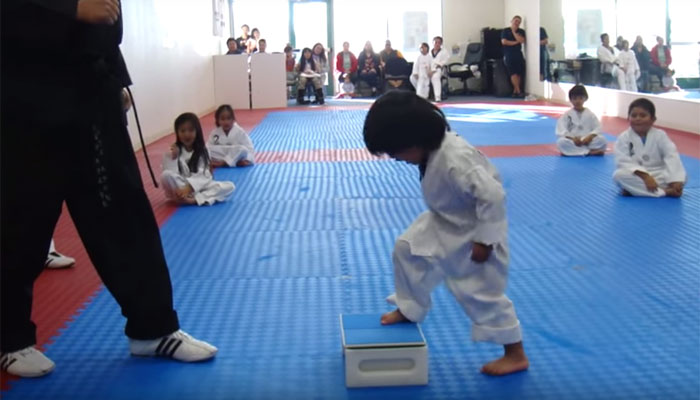 Three-year-old attempting to break board